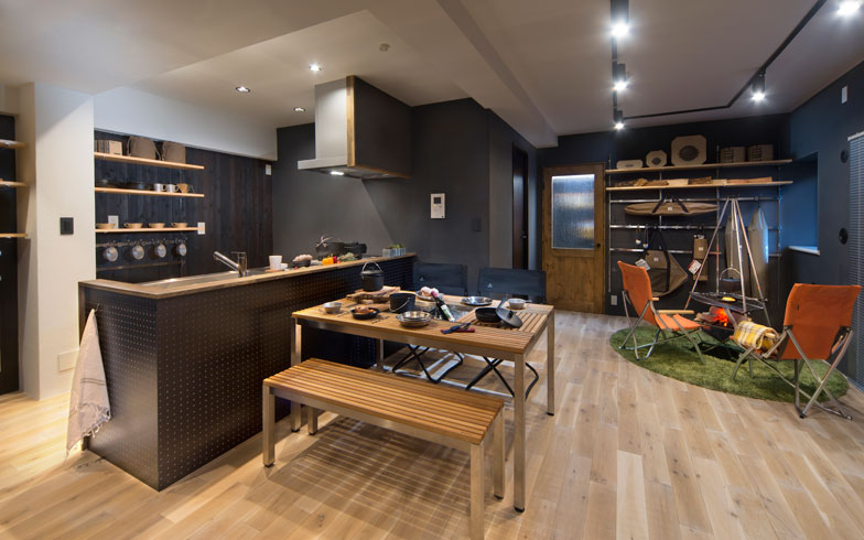 【画像1】Snow Peakとリノベ不動産の初コラボ作品である横浜のマンション。築19年の部屋が快適なアウトドアフィールドに変身。無垢材と漆喰(しっくい)壁の風合いある空間に、テーブル&ベンチ、ローチェアなど、Snow Peakのガーデン家具を合わせ、キャンプ場に来たかのようなワクワク感を生み出しました(写真提供/リノベ不動産)