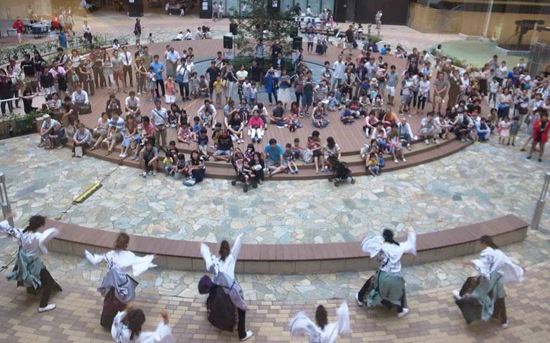 【画像2】住宅棟、オフィス棟、コミュニティ棟など7棟からなる建物の中庭・オアシスコートが「空庭祭」のメイン会場となった。事業主であるデベロッパーの社員も所属する、よさこいの演舞が披露された(写真撮影/村島正彦)