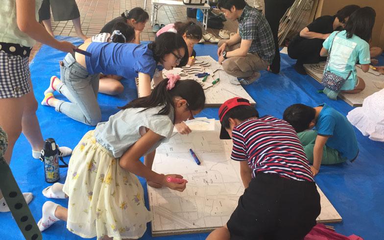 【画像6】子ども向けのワークショップでは、段ボールを利用してジオラマ地図を製作。近隣の地形の高低差を3次元で実感するのが目的だ。その後、地図上で災害時の避難シミュレーションなどが行われた(写真撮影/上島寿子)