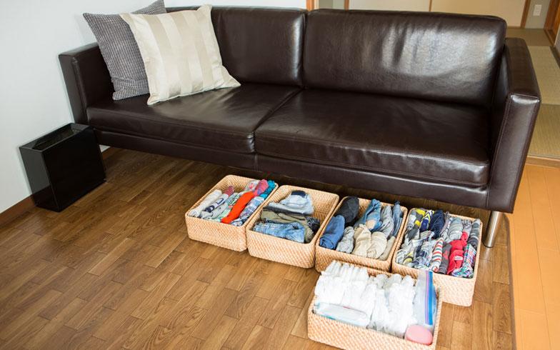 【画像4】期間限定で使用する子ども用家具を買う代わりに、ソファ下にカゴを並べて子どもの衣類やおむつを収納。子どもが大きくなったら、カゴは別の場所で使うこともできます(写真撮影/片山貴博)