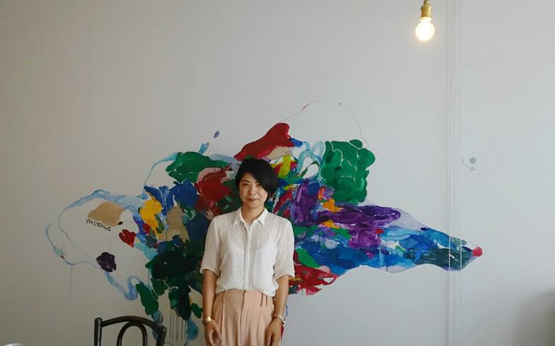 【画像1】岸本千佳さん。友人のアーティストに頼んで書いてもらったイラストが印象的な事務所で話を伺った(写真撮影/四宮朱美)