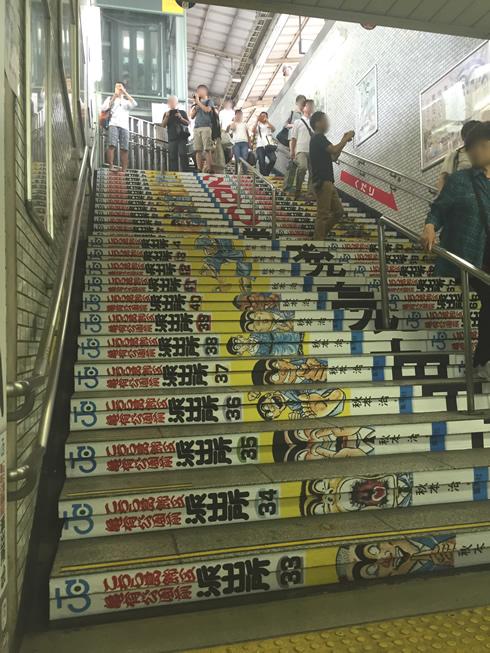 【画像1】階段には単行本の背表紙がズラリ。記念にと撮影する人の姿が絶えない(写真撮影/SUUMOジャーナル編集部)