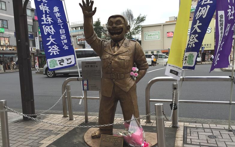 【画像3】亀有駅北口にいる両津勘吉像には、誰が置いたのか花束が。ちなみにこれが2006年、亀有に初めて誕生した両さん像(写真撮影/SUUMOジャーナル編集部)