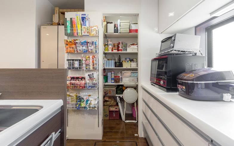 【画像6】動線を考え180度扉が開くように設計したパントリーは食材の出し入れがしやすく大変重宝しているそう。妻の「収納を多くしてごちゃごちゃした物を隠したい」という希望で実現した(写真撮影/杉浦幹雄)