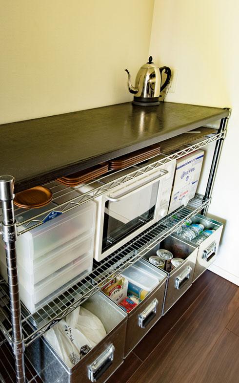 【画像7】天面を広く使うため、電子オーブンレンジはスチールラックの中段に。最下段に「無印良品」の「トタンボックス」を並べ、お米や食品、水などのストックを収納。最下段と床の間には、ルンバのホームベースを設置(写真撮影/片山貴博)