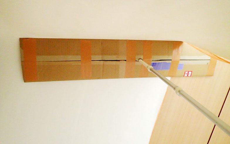 【画像8】床掃除用のフロアワイパーを段ボールで長くした道具が、壁紙を支えるのに便利でした(写真撮影/玉置豊)