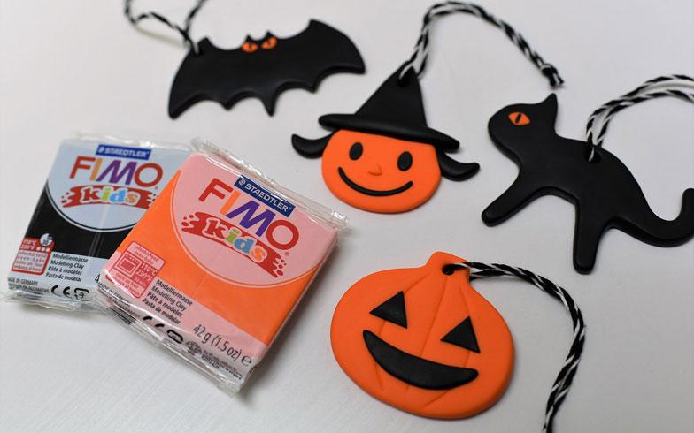 【画像12】子どもでも簡単につくれるやわらかい粘土「FIMOシリーズのキッズ」(1個356円/税込)。成型後、オーブンで加熱して仕上げるとプレート状になる。オーナメント、ブローチ、指輪、なんでもつくれる。写真は「オレンジと黒の2色だけでけっこういろいろつくれますよ」と森井さんがつくってくれた作品。かわいい!(写真撮影/榎並紀行)
