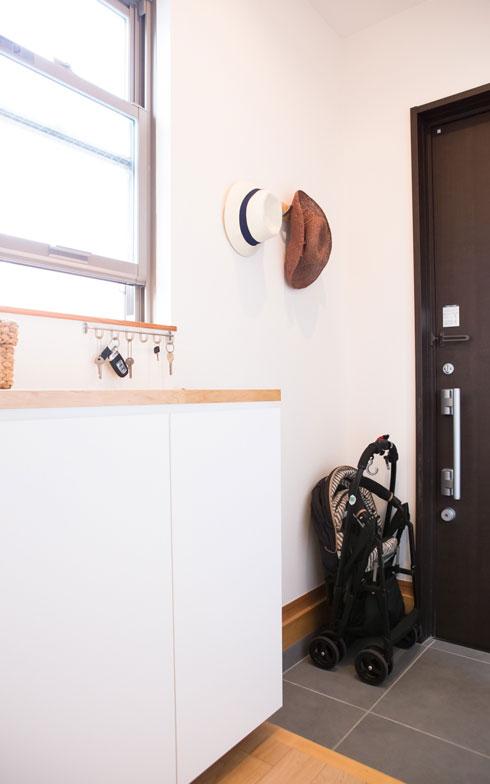 【画像3】玄関は下駄箱をオーダーし、靴脱ぎの場所と箱の面をそろえて、すっきりと。靴箱のなかには傘や虫よけなど、生活感のあるものが収まる(写真撮影/片山貴博)