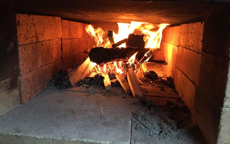 【画像1】薪を燃やしてしっかり予熱をとる。十分温まれば燃料を取り出しても調理できる。家庭用石窯キットなど開口部や炉自体が小さな石窯の場合は炭を利用する(写真提供/石谷林業薪クラブ)