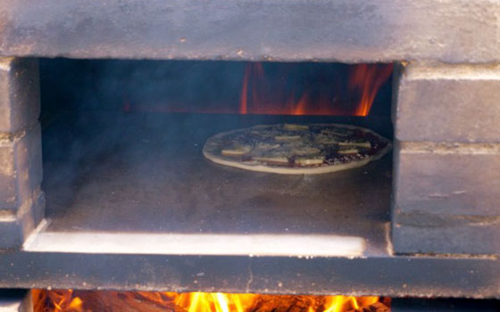 【画像8】石窯内で焼かれるピッツァ。着火してから適温近くになるまで1時間半かかっている(写真提供/そーたろさん)