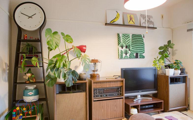 【画像2】年代物の大きなオーディオセットとIKEAの大きな時計、その周りには小さな雑貨や植物が飾られているリビングスペース。古いものと新しいもの、大きなものと小さなものがバランスよく融合しています(写真撮影/片山貴博)