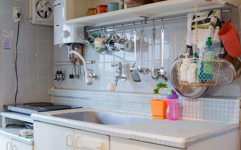 【画像4】シンクまわりの天面にDIYでタイルを貼り付け、使いづらかった水栓は好みのものに取り替えました。シンク上に付いていた水切り棚を外してレールを取り付け、よく使うキッチンツールやマグカップなどをかけて収納(写真撮影/片山貴博)
