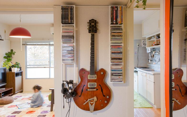 【画像8】Makeesさんの愛器、「カントリージェントルマン」の両脇に取り付けたCDラックも手づくり。壁掛けしているギターの位置は、「子どもがいたずらするので、少し高い位置に取り付けなおしたんです(笑)」(写真撮影/片山貴博)
