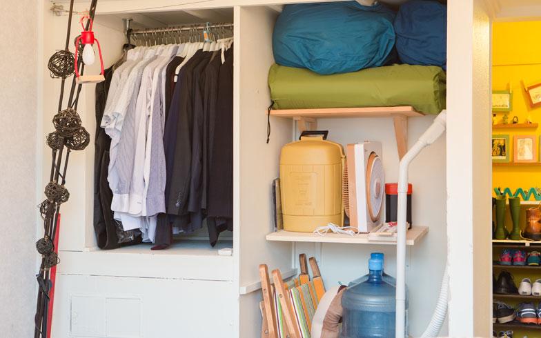 【画像12】玄関横にある寝室の収納スペースも、扉を取り払ってオープンに。左手はMakeesさんのスーツ類。右手は最近はじめたキャンプ道具の一部。収納力をあげるため、さらなるDIYを計画中だとか(写真撮影/片山貴博)