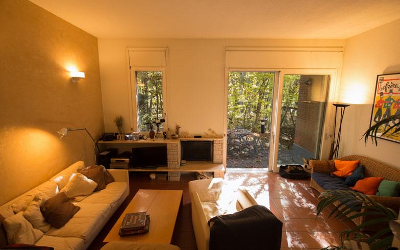 【画像 8】「家具はほとんどオフィスで使っていたのを持ってきた程度」。アルフレックス社のソファに落ち着いた間接照明、暖炉もあるリビングルーム(写真撮影/片山貴博)