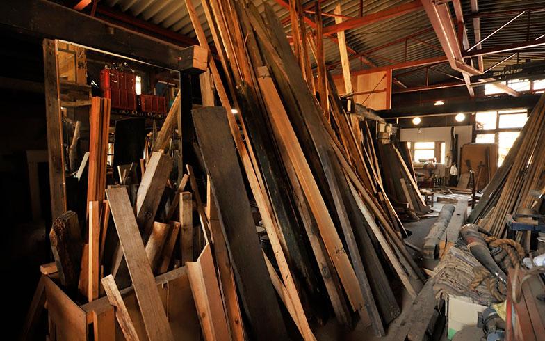 【画像11】母屋の内装は最近やっと手を付け始めたところ。そのため、木材や機材・工具で埋め尽くされていた。材木は古民家を解体して集めたため、かなり年期が入っている(写真撮影/松倉広治)