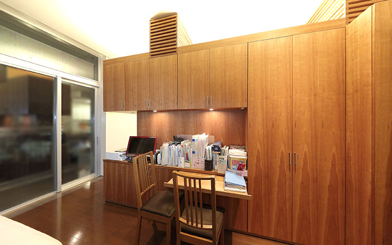 【画像3】造作家具の寝室スペース側は一部を凹ませて、書斎コーナーに。照明を埋め込んでデスクまわりの明るさを確保。デスクは引き出し式なので、使わないときはすっきりと片付けておけます(写真撮影/飯田照明)
