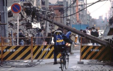 【画像3】阪神淡路大震災発生時の様子。倒壊した電柱が通行人の進路をふさいでいる(画像提供/NPO法人 電線のない街づくり支援ネットワーク)
