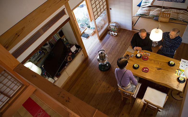 【画像7】2階の吹抜けから見下ろせるリビングで談笑するKさん(右上)とC子さん(左下)、田空間工作所取締役社長の関謙二さん(左上)。机や椅子もすべて、田空間工作所で製作した。リビングは、床暖房のおかげで冬はエアコン要らず。屋根に空気の通り道を設けたことで、夏も涼しい(写真撮影/片山貴博)