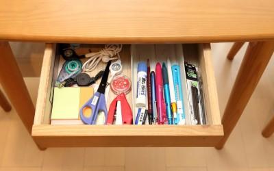 【画像2】テーブルの引き出しには家族がよく使うボールペン、はさみ、のり、ホッチキス、消しゴム、など厳選された文房具一式がまとめられている。ストックの文房具は、ボールペン、スティックのりなどそれぞれまとめて輪ゴムでしっかりまとめて別の引き出しに入れ、なくなったらストックから補充(写真撮影/飯田照明)