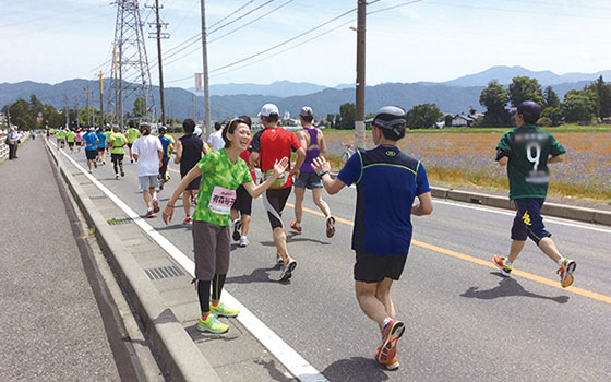 【画像1】国内のマラソン大会でランナーたちに声援をおくる有森さん(写真提供/有森裕子さん)