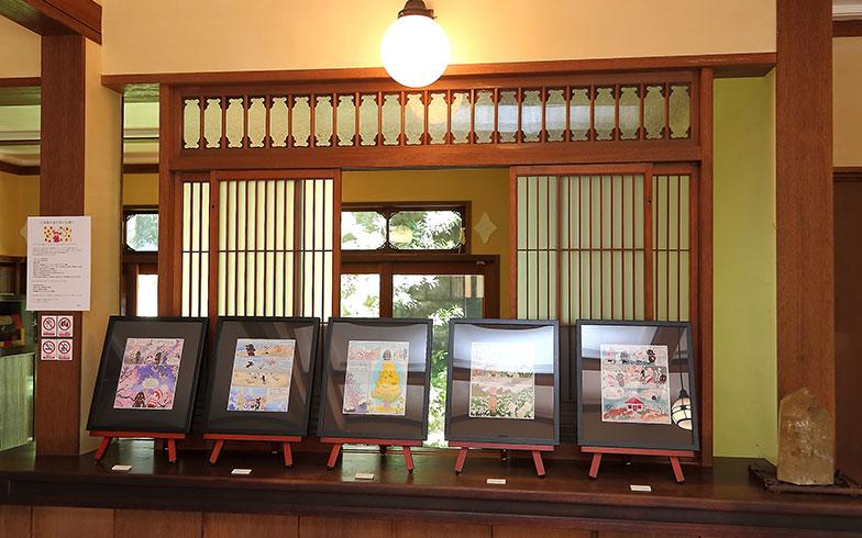 【画像4】今まで目にしていた印刷物に比べて原画が色鮮やかで色味も複雑だ。原画が飾ってあるカウンターは桜の古材を使用した一枚板、正面の木製建具は安野さんがこだわって集めた逸品(写真撮影/飯田照明)