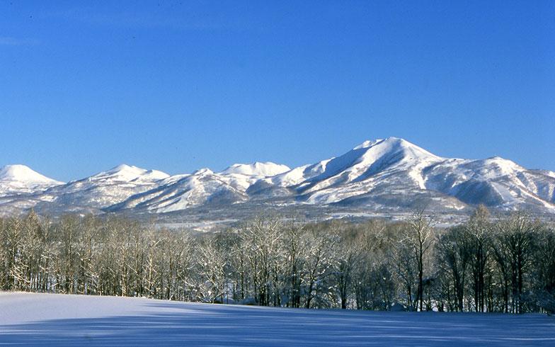【画像3】冠雪した山並みの美しさも魅力のニセコアンヌプリ。スキー場の周辺には別荘やコンドミニアムが点在する(写真提供/倶知安観光協会)