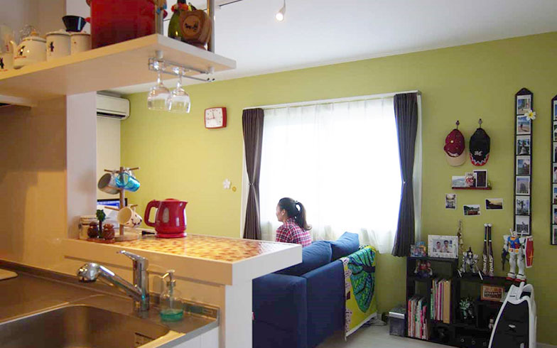 【画像2】ヒカリハイツに暮らすNさんご夫妻のリビング。黄色の壁紙は、インテリアコーディネーターの資格をもつNさんが部屋や家具に合うように選んだ。手前のキッチンカウンターは赤や黄色のガラスタイルで、これは当初からの内装だ(写真撮影/村島正彦)
