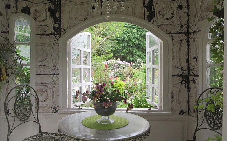 【画像4】小屋の中はテーブル&チェアと、お気に入りの小物が飾られたすてきな小空間。窓から見える景色が絵画のよう(写真撮影/藤井繁子)