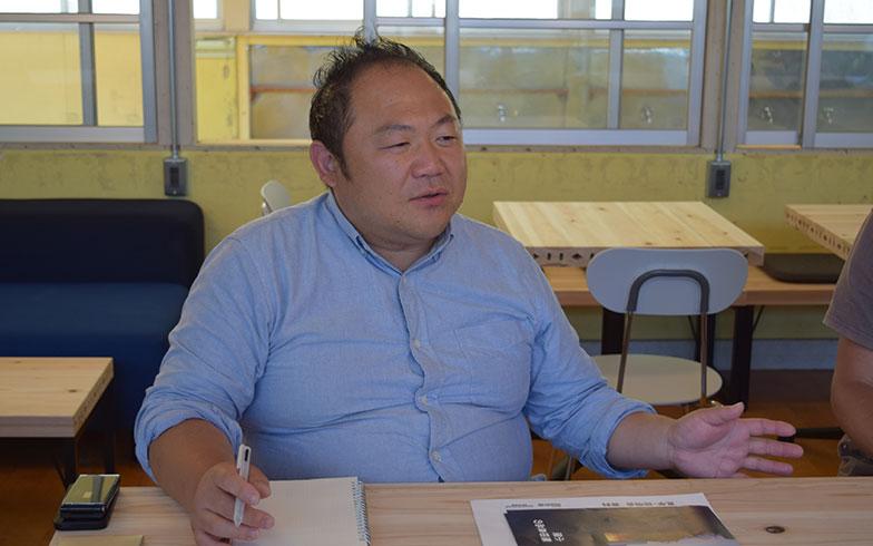"""【画像7】良品計画の高橋哲さん。現在、シラハマ校舎の現場担当者を務めているが、自身も南房総市に隣接する鴨川市に移住しており、""""一人事務所""""で働いている。「緑に囲まれて鳥のさえずりが聞こえて…仕事が捗って仕方ありません」と話す(撮影/末吉陽子)"""