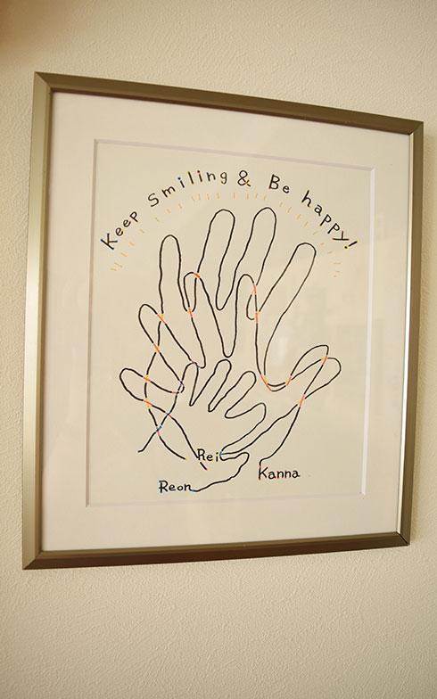 【画像17】装飾担当の方がオリジナルで描いたという家族3人の手が重なったすてきな絵。家族の強い絆を連想させる絵は、今後の展開を暗示しているのかも?(撮影/末吉陽子)