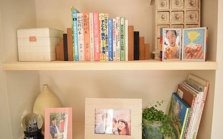 【画像19】ベッドサイドの棚には家族写真や絵本、そして子どもの病気にまつわる本が置かれている。ここにも、子ども思いで勉強熱心なカンナさんの一面が(撮影/末吉陽子)