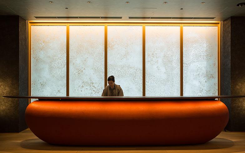 【画像3】紙吹雪の柄をイメージした「手すき和紙」のウォールと、木材をかさねて曲線美を演出したエントランスカウンター。落ち着いた色味は「弁柄(べんがら)」と呼ばれる顔料を混ぜ、左官職人が3度塗りして仕上げた。日本の赤をイメージしているという(撮影/片山貴博)