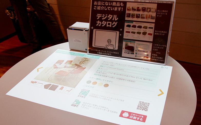 【画像2】期間限定で設置されているプロジェクター型デジタルカタログ。テーブルに映し出されたカタログをタッチパネル感覚で操作しながら商品を選べる(写真撮影/前川ミチコ)