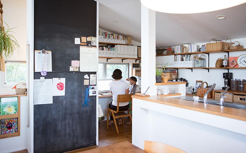 【画像4】キッチンの横には、家族の書斎スペースを設けています。壁面ぴったりに収まっている長いデスクはDIYでつくったもの。壁に取り付けたオープンシェルフもDIYだそうです(写真撮影/片山貴博)