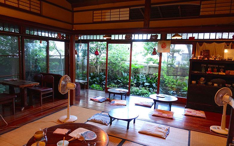 【画像1】L字の広縁。木枠の窓が古の風情を感じさせ、2方向に開いた窓から海風が入ります。畳にちゃぶ台、団扇と扇風機…。古き良き日本の暮らしが凝縮された空間です(写真撮影/金井直子)