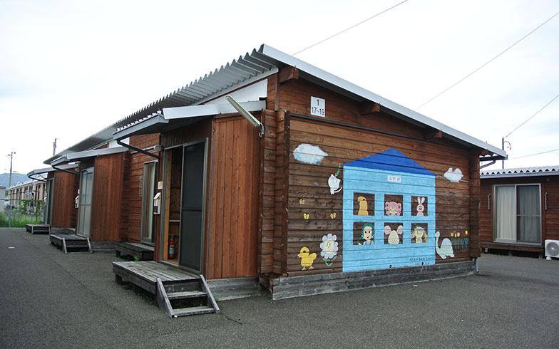 【画像2】福島県福島市飯坂町で地元工務店により建設された木造仮設住宅。いろいろなタイプがあるが、画像2は、ログハウス工法によるもの。外壁の絵は地元の高校の美術部の生徒が描いた(写真撮影/筆者)