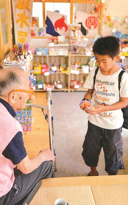 【画像6】駄菓子屋さんの店番をする入居者と遊びに来た子ども。駄菓子屋にはおどろくほどたくさんの種類の駄菓子が用意されていて、大人も子どもも楽しめる(画像提供/シルバーウッド・下河原忠道さん)