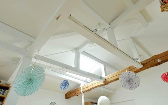 【画像3】天井を高くしたかったというNさん。解体してから出てきた丸太梁(まるたばり)をそのまま活かしている部分と、白くペイントした部分に分け、デザイン性の高い仕上がりに。また、天窓をつけて室内に光を取り込んでいる(撮影/森カズシゲ)