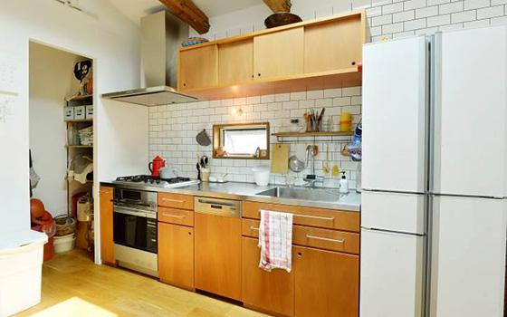 【画像4】木目のナチュラルな質感がおしゃれなキッチンは造作。ドイツ製「Miele(ミーレ)」の食洗機もビルトインしている。壁面にはタイルを貼り、見せ方にも工夫を感じられる(撮影/森カズシゲ)