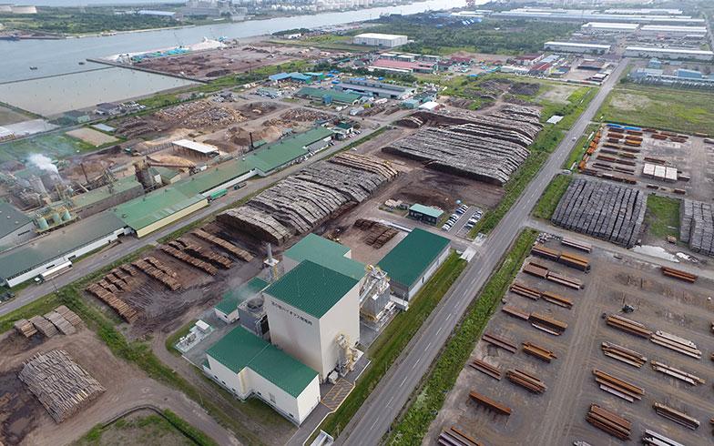 【画像8】北海道苫小牧市にある苫小牧バイオマス発電所。発電規模は5.9MW、年間送電量は約400万kWhで一般家庭約1万世帯分の年間使用電力量に相当する。敷地内に積まれた木材は約10万tで約1年半で使い切る量だ。(画像提供/苫小牧バイオマス発電株式会社)