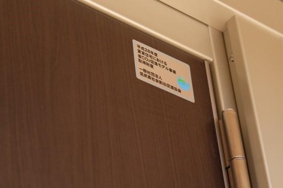 【画像1】「グリーンガーデン稲荷山」のエントランスのドアには、省CO2住宅として認められた賃貸住宅を示すステッカーが貼られている(写真撮影/籠島康弘)