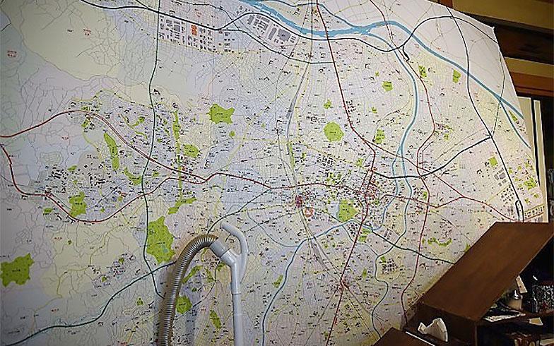 【画像2】自宅には壁一面を覆い尽くすほどの紙の地図もあった。手前の掃除機と比較すると、その巨大さがよく分かる(撮影/榎並紀行)