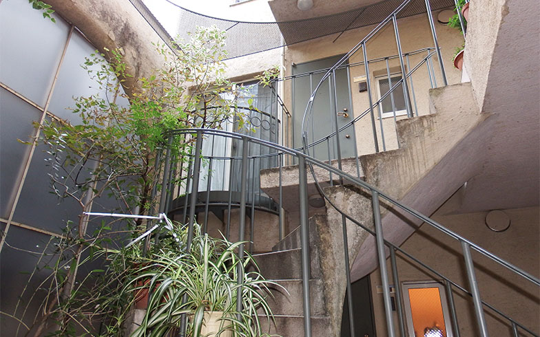 【画像2】多くの場合、中庭から上階の部屋へはらせん階段などで入る。曲線や植栽のおかげで自然に抱かれて暮らす感覚もある(写真撮影/織田孝一)