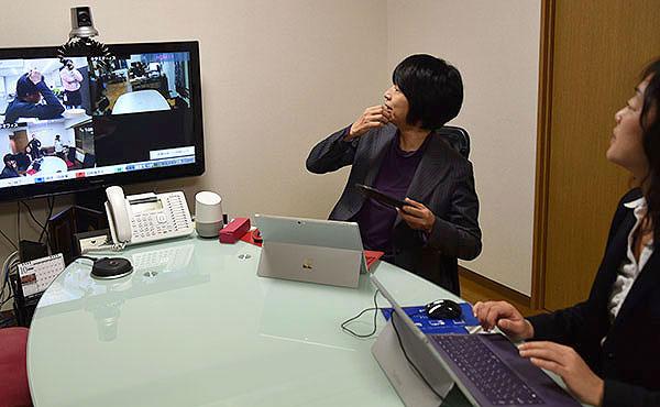 【画像1】東京のオフィスにあるテレビ会議で、北海道のオフィスや奈良のテレワークセンターの様子を確認する田澤さん(左) (撮影/周東淑子)