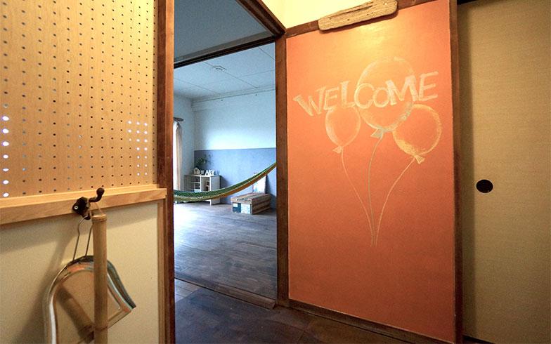 【画像7】ウェルカムボードがかわいい大井さんの部屋は、DIYやセルフリノベーションに興味がある人々を募り、ワークショップ形式でリノベーションした。奥のリビングにはハンモックが。ここで揺られながら仕事をすれば、リラックスしてよいアイデアが生まれるのだそう(写真撮影/蜂谷智子)