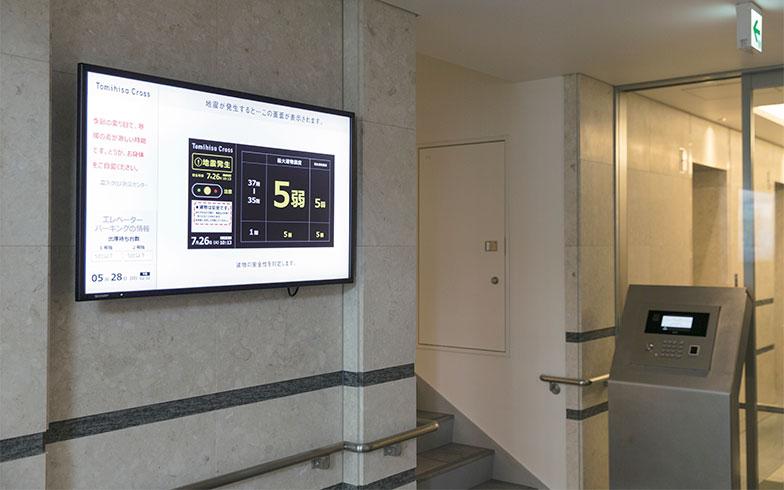 【画像3】1階エレベーターホール脇のサイネージ。地震発生時には、建物の状態が表示される。各フロアのエレベーターホールにも、同様のモニターが設置されている(写真撮影/川瀬一絵)