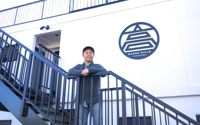 【画像1】「しぇあひるず ヨコハマ」の大家さん、荒井聖輝さん。モノトーンの外観に、デザインされたロゴが映える建物。しっかりと耐震補強している故に壁が厚くなっているそう(写真撮影/蜂谷智子)