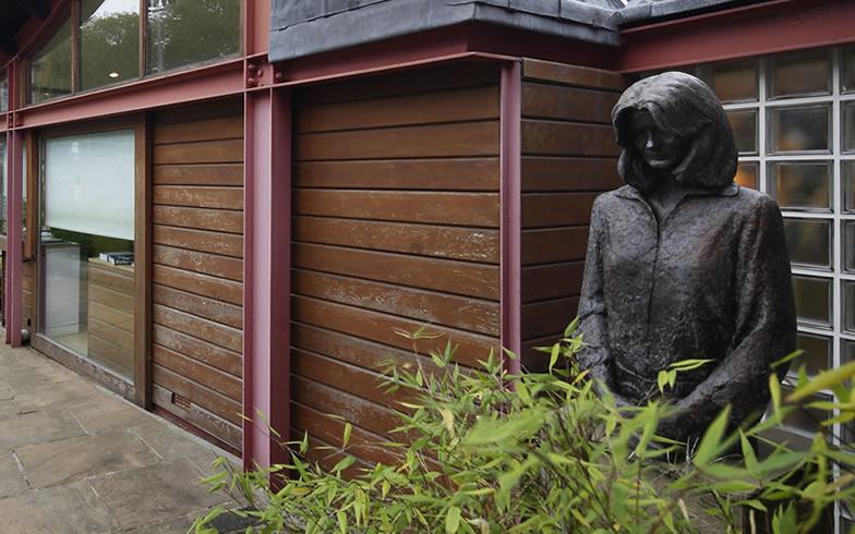 【画像1】センターの庭に立つマギーの像。1941年スコットランド生まれ、1995年「マギーズ・センター」オープンの前年に54歳で旅立った。センターの前身である病院内の小屋の前で、春の日を浴び「私たち、ラッキーよね?」と言葉を残して(写真提供/藤井浩司(ナカサアンドパートナーズ))