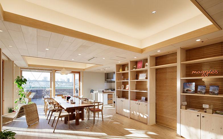 【画像3】日当たりの良いオープンなダイニングとキッチン(右手の奥)。折り上げ天井で空間に変化と豊かさを創り出し、アフリカンチェリーの大きな一枚板のテーブルや柳宗理デザインの和紙の照明などが空間のクオリティを高めている(写真提供/藤井浩司(ナカサアンドパートナーズ))